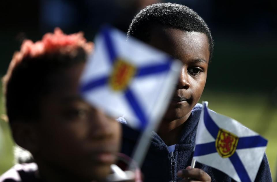 Freddy Smith, 9, of Dorchester (right) waved the flag of Nova Scotia as the tree arrived on Boston Common.